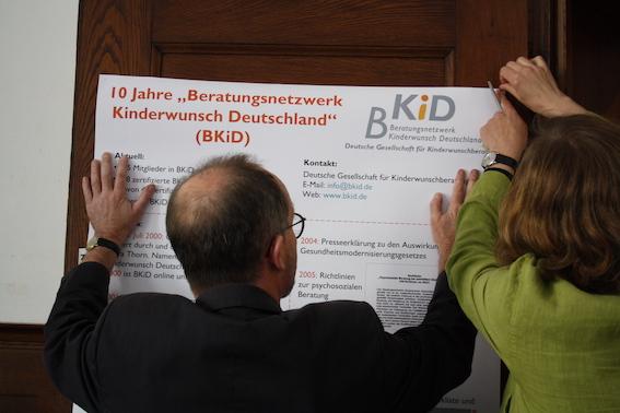 Tewes Wischmann und Doris Wallraff hängen ein BKiD Poster auf