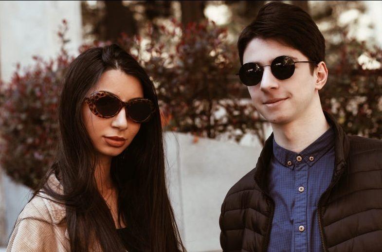 woman in black sunglasses and brown coat